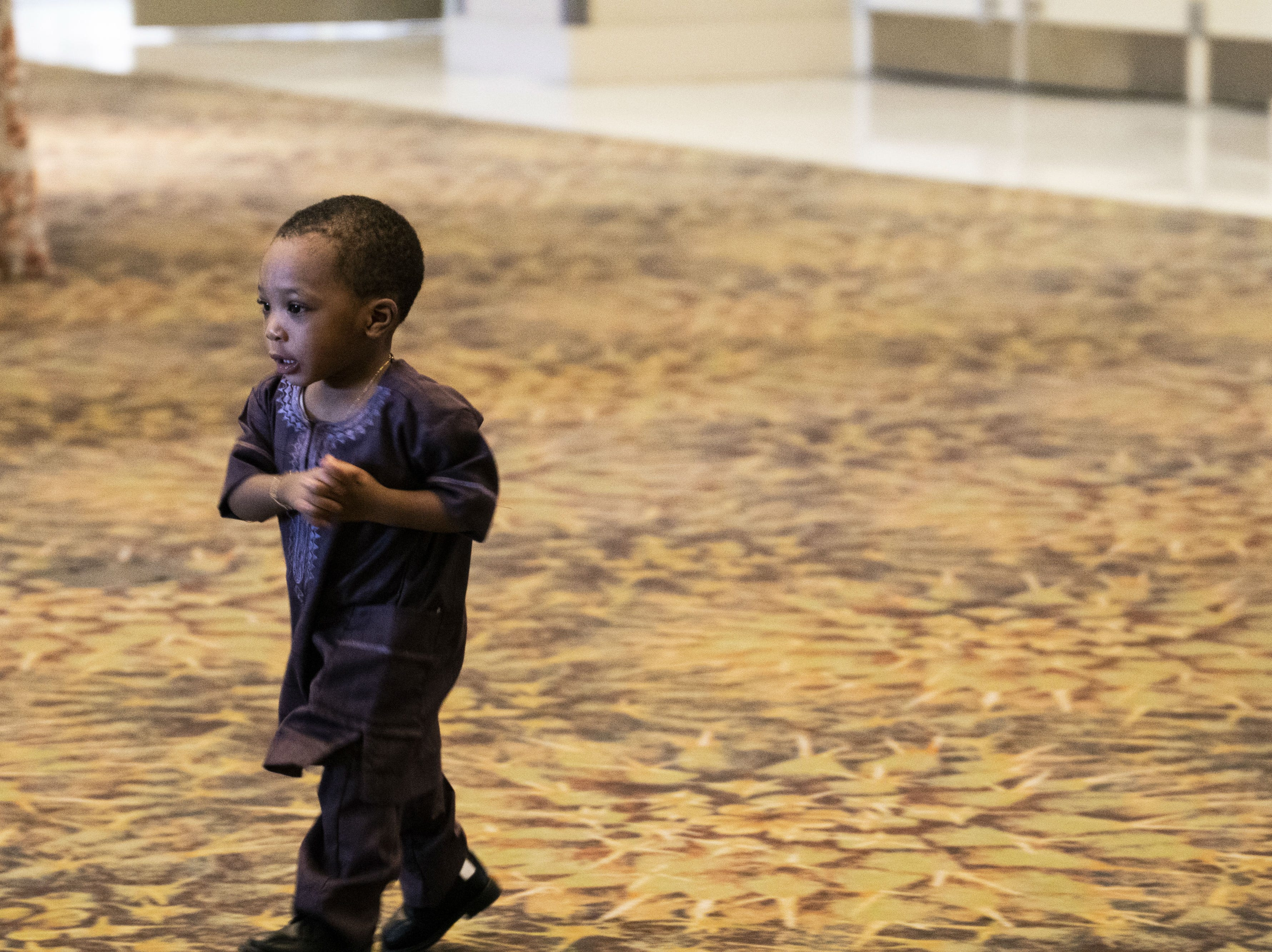 A boy runs around the convention center during an Eid celebration on Aug. 21, 2018, in Phoenix.