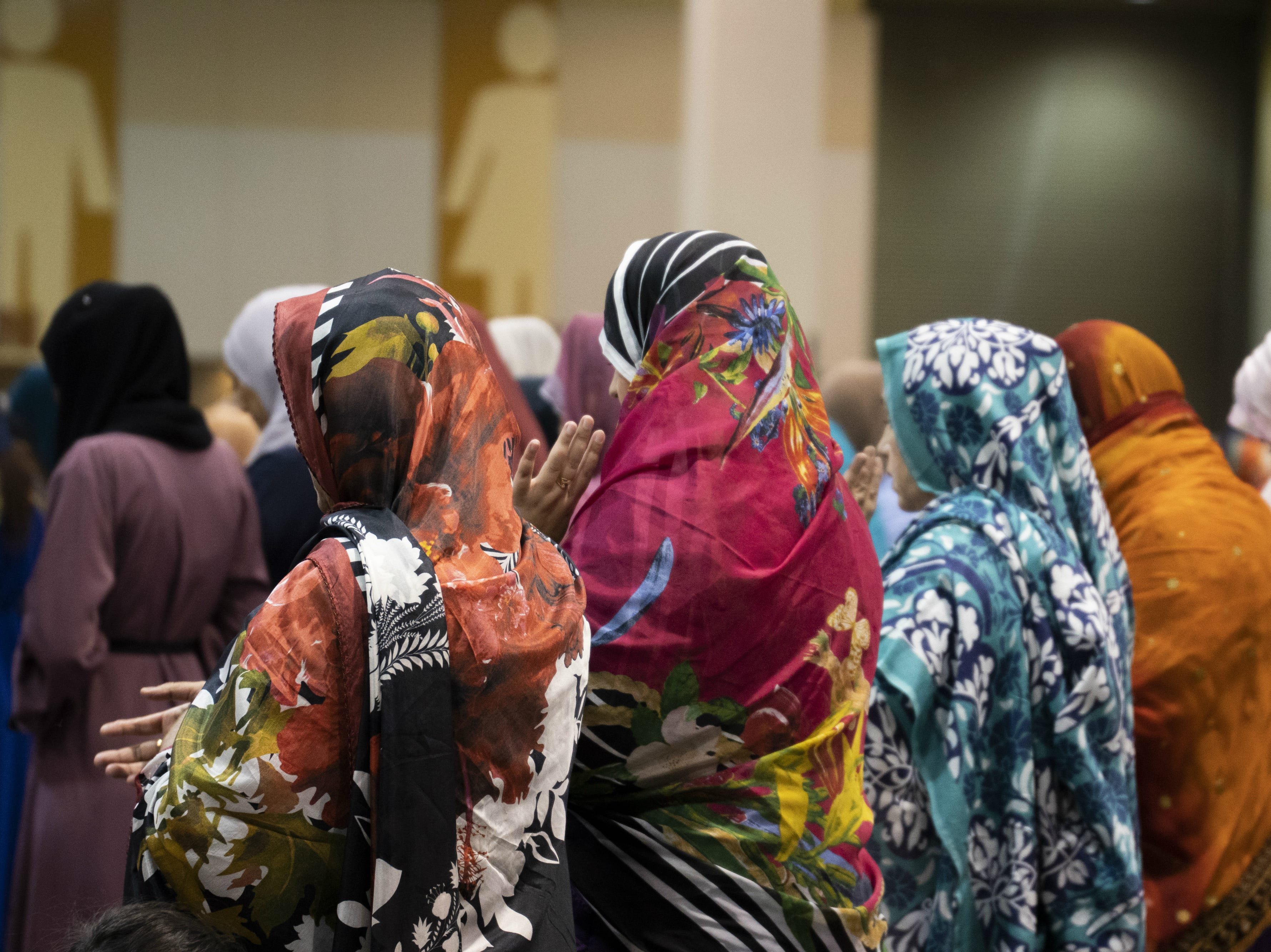Women in colorful hijabs pray during an Eid celebration on Aug. 21, 2018, in Phoenix.