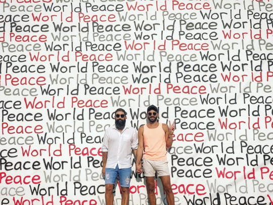 David Duran poses in front of a downtown Phoenix mural with his partner, David Saccoccio.