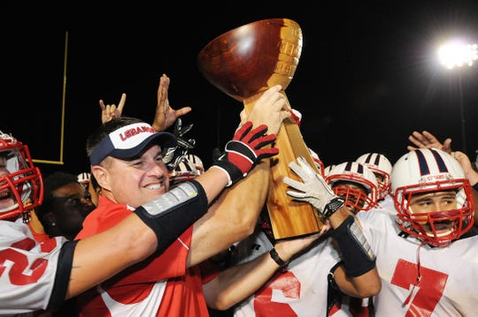 Lebanon head coach Gerry Yonchiuk hoists the Cedar Bowl trophy after the Cedars were victorious in the 2011 game.