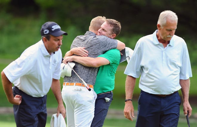 Noah Firestone, second from left, gets a hug from his partner Chris Gebhard after they defeated Greg Ulp, left, and Rick Troutman for their second straight W.B.Sullivan Four-ball Invitational championship at the Lebanon Country Club Monday August 20, 2018.