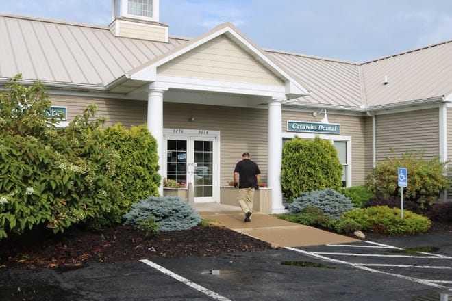 A law enforcement agent enters the offices of Catawba Dental, 3274 NE Catawba Rd., on Tuesday as part of a joint investigation.