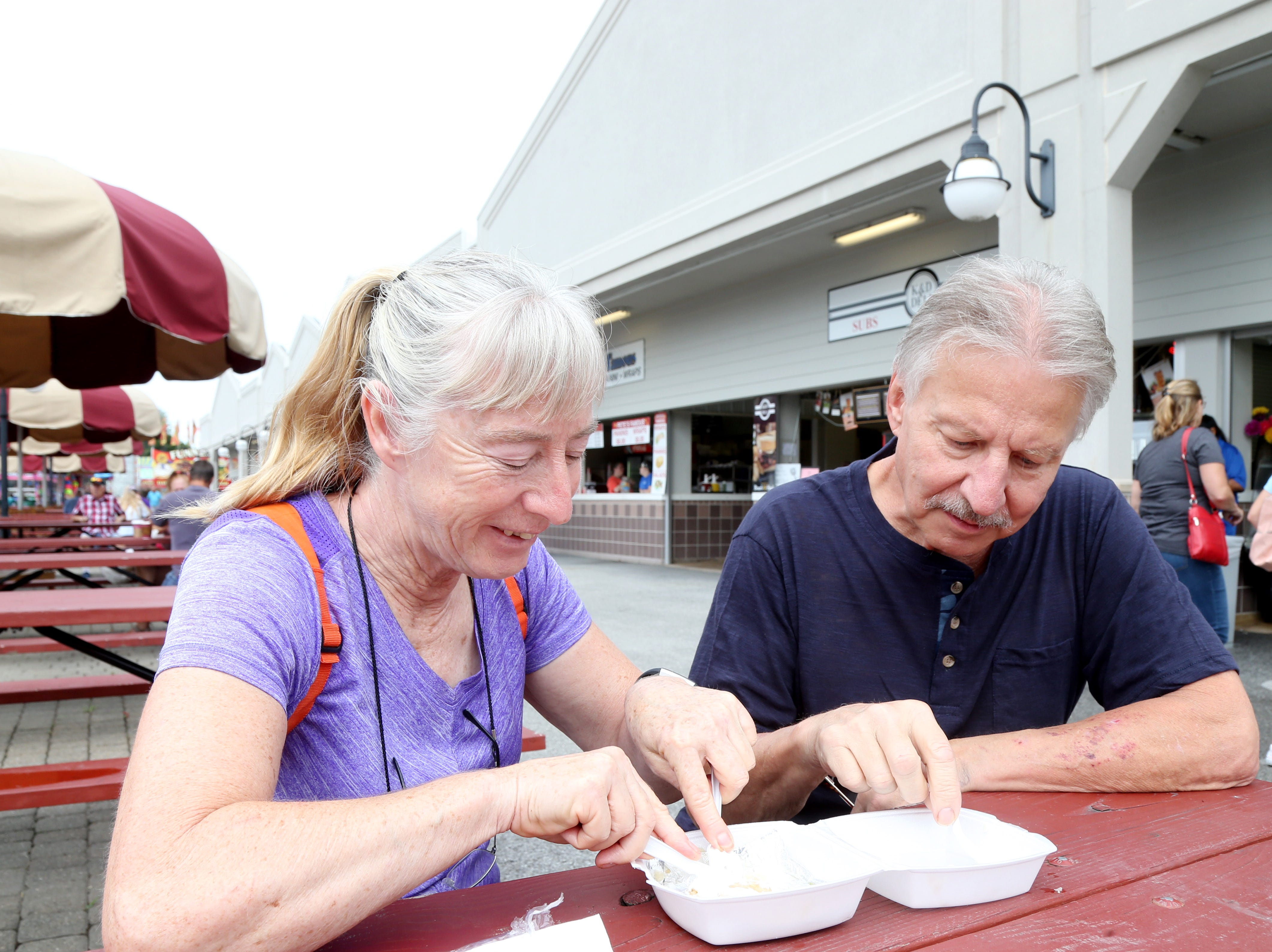 Donna Anderson of Lake Carmel and Joe Staniszewski of Fishkill enjoy the lack of big crowds and the food on the opening day of the Dutchess County Fair in Rhinebeck on August 21 2018.
