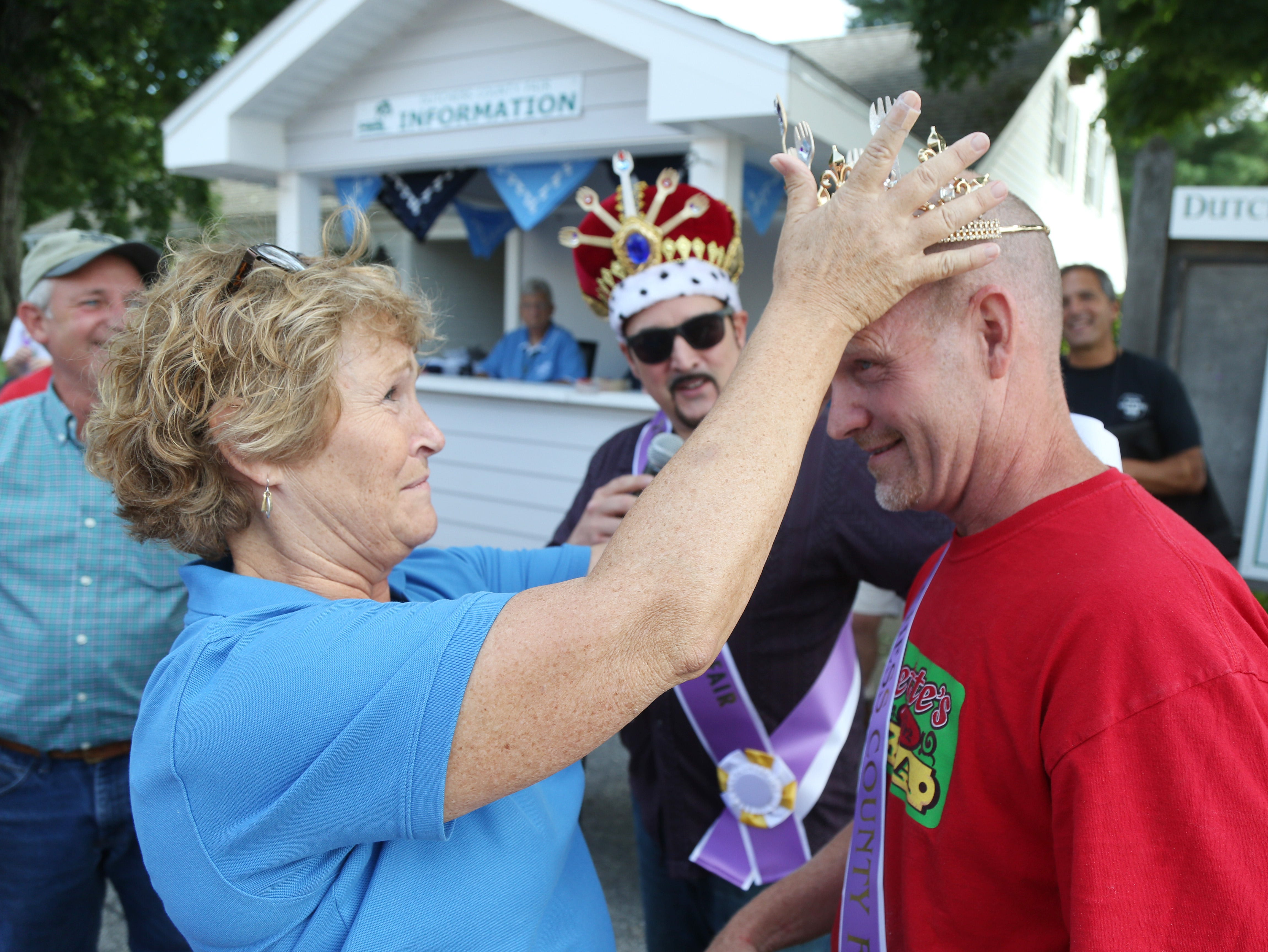 Deb Ashmann, vendor manager crowns Brian Gillette for winning the Sporkrun competition on the opening day of the Dutchess County Fair in Rhinebeck on August 21 2018.  Gillette, of Oneonta won with his daughter's creation, a bacon macaroni and cheese calzone.