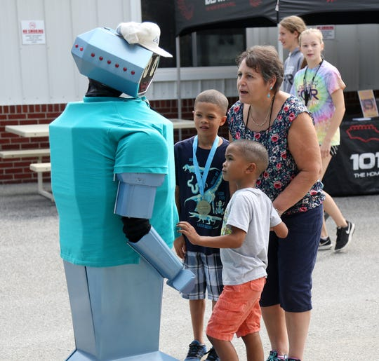 From left, Sean and Specner Blackmon of Connecticut with their grandmother, Lucia Pitras of Millbrook have a chat with Oscar the Roving Robot on the opening day of the Dutchess County Fair in Rhinebeck on August 21 2018.