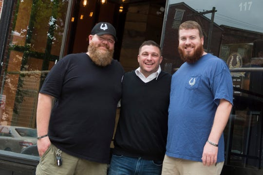 From left: Gift Horse co-owners Jason Snyder and Casey Brenner, and manager Zach St. John pose outside of Gift Horse Brewing Company in downtown York.