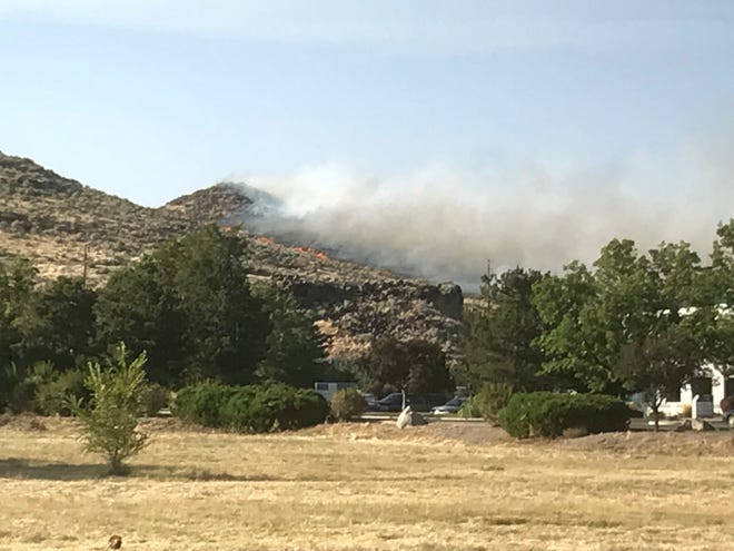 A brushfire burns on the hills south of Huffaker Park in Reno.