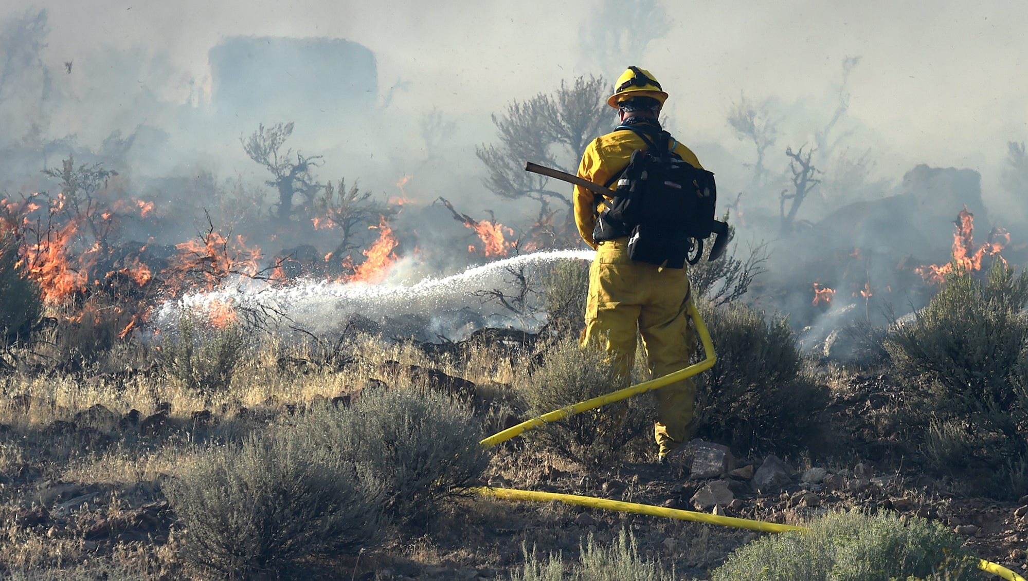 A firefighter hoses down a brush fire on the hills behind the IGT building in Reno on Monday afternoon on August 20, 2018.