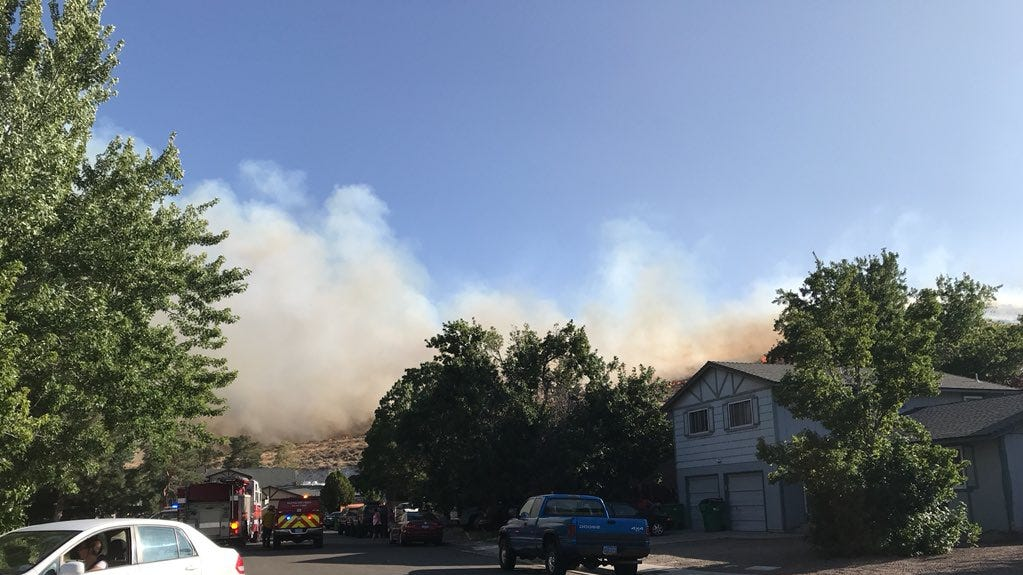 A fire burns near homes in South Reno on Monday.