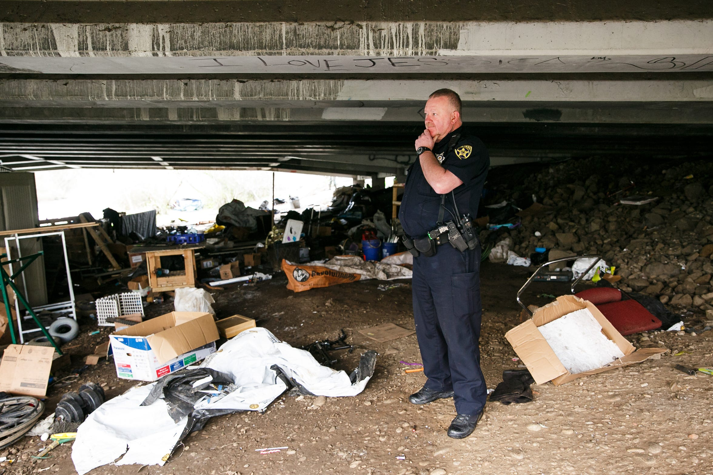 Salem Police Office Bob Owings surveys what's left of a homeless camp under the Highway 22 overpass that crosses Mill Creek near Costco and Lowe's Jan. 29, 2018.