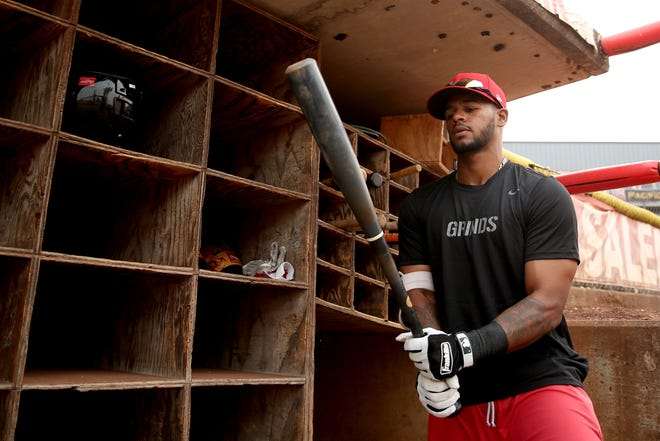 Salem-Keizer Volcanoes outfielder Christopher Burks demonstrates one of his baseball rituals, putting on his batting gloves, shin guard and elbow guard the same way before each at bat at Volcanoes Stadium in Keizer on Monday, Aug. 20, 2018.