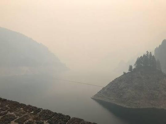 Smoke engulfs Cougar Reservoir due to a new wildfire.