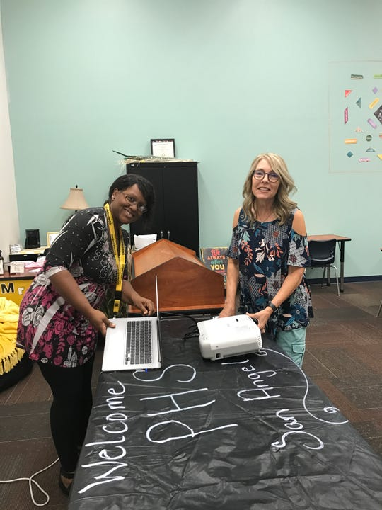 Lead teacher Evelyn Bonner (left) and aide Shelly Salling (right) finish decorating Premier High School in Sunset Plaza, 4102 Sunset Drive.