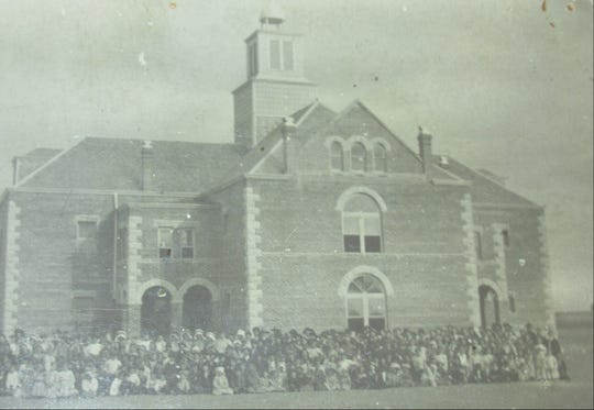 Students pose in front of the two-story brick building with its bell tower at the Miles school in 1906.