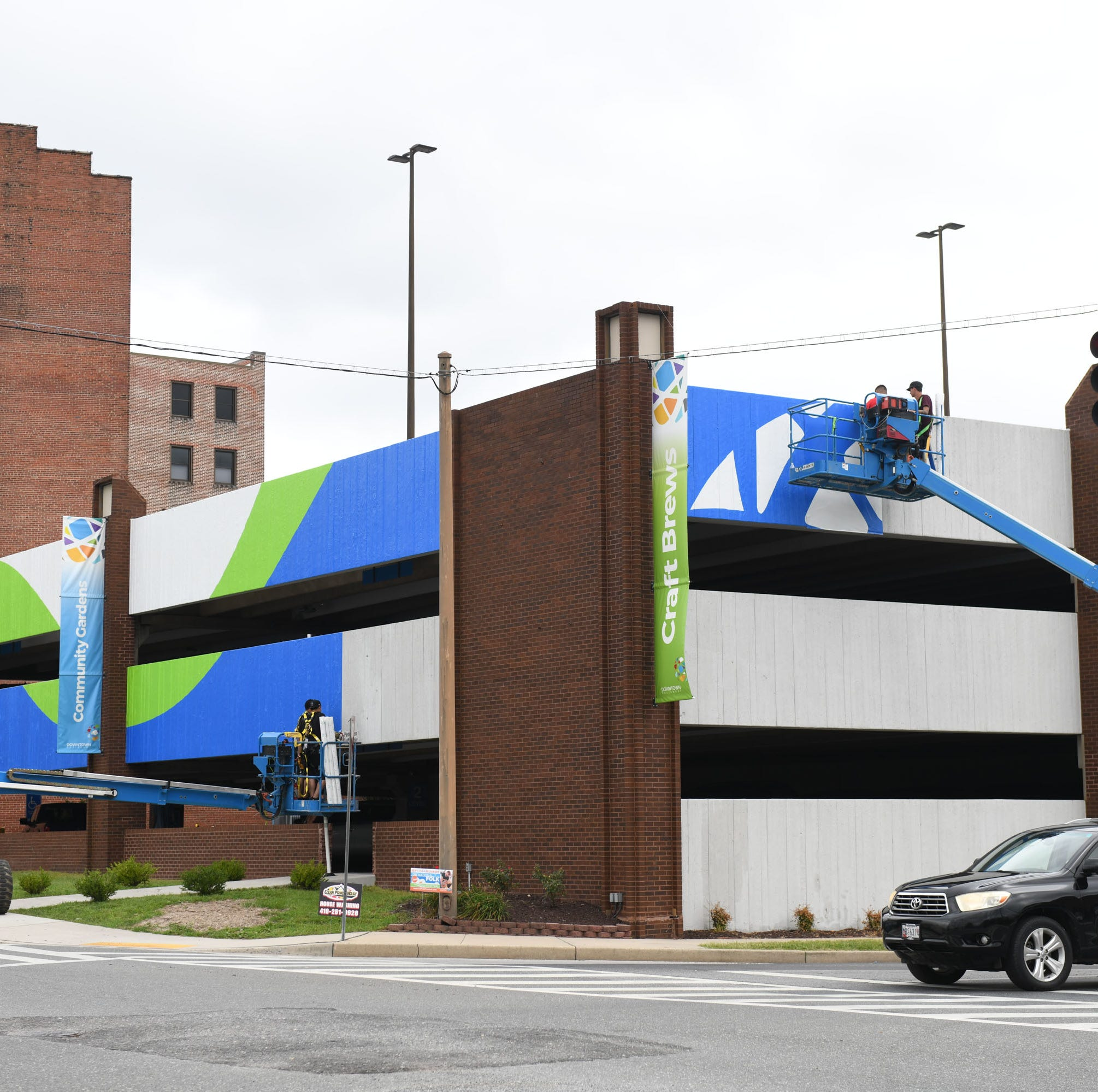 A contractor began wrapping the Salisbury parking garage in a material that will adhere to the concrete. The design incorporates colors and patterns used in the city's new marketing materials and logo. Improvements are being made in time for the upcoming National Folk Festival.