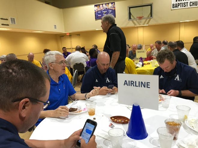 Airline coaches check their cell phones prior to Monday's Lion's Club Jamboree coaches' dinner.