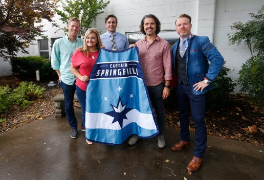 Janelle Reed, the outreach and special events manager for Victory Mission, is presented a Captain Springfield cape by (from left) Jeff Houghton, Joel Thomas, John McQueary and Sean Brownfield.