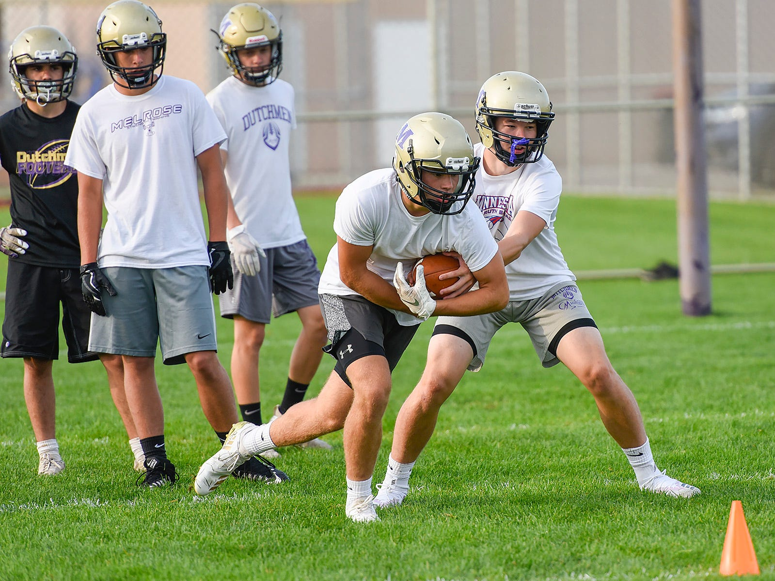 Melrose back Adam Helmin takes the ball from quarterback Reegan Nelson Wednesday, Aug. 15, during practice.