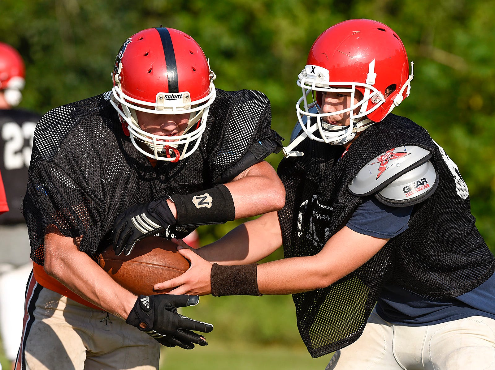 Milaca's Tyler Thebiay takes the handoff form quarterback Louis Rudolph-Munson Thursday, Aug. 16, in Milaca.