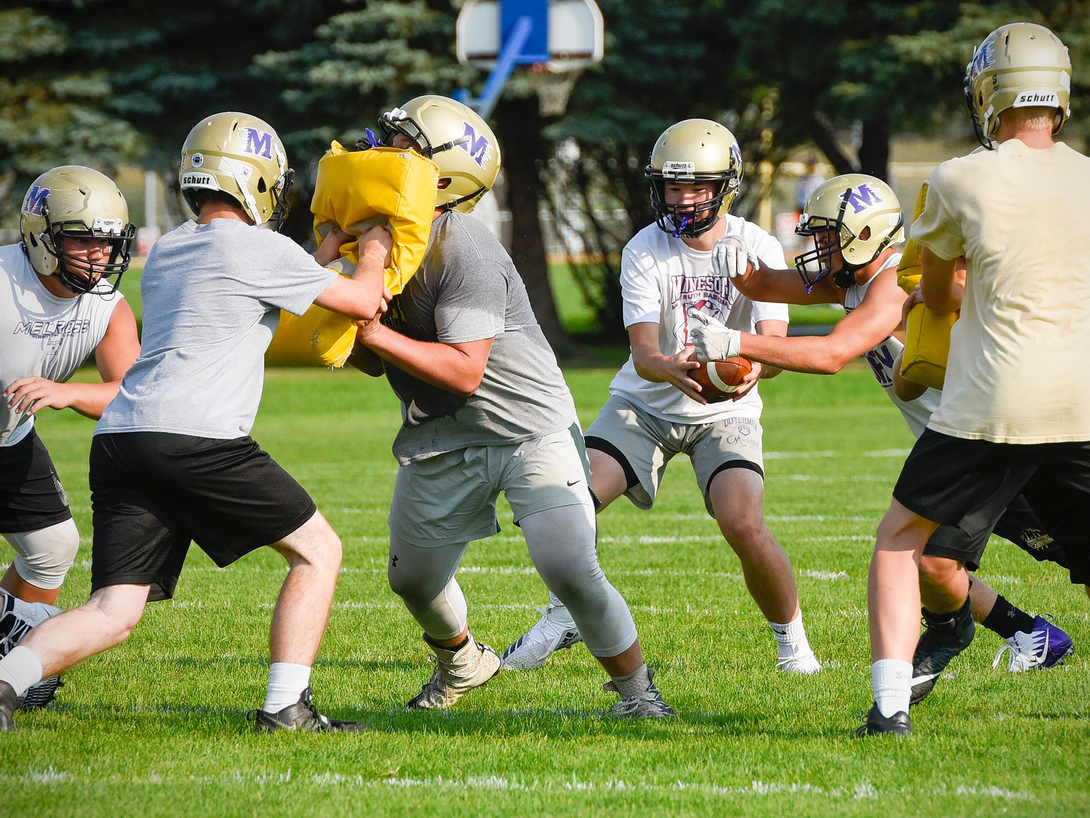 Melrose quarterback Reegan Nelson hands off the ball on a play Wednesday, Aug. 15, during practice.
