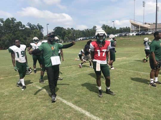 FAMU backup quarterback Resean McKay of Godby High School watches as head coach Willie Simmons calls in plays.