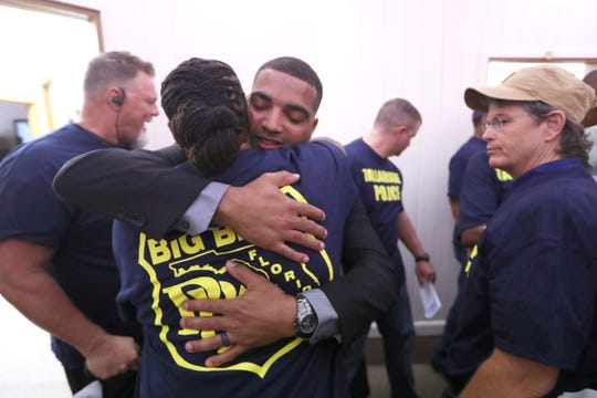 Former Tallahassee Police officer Damien Pearson is hugged by fellow officer Tysha Gates, one of the dozens of supporters at the Big Bend Police Benevolent Association as they question Pearson's recent firing Tuesday, Aug. 21, 2018.