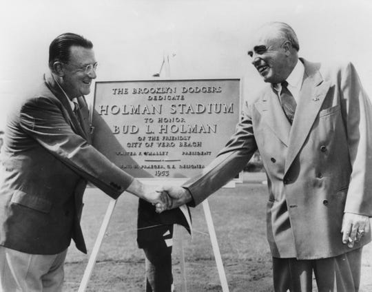 "Walter O'Malley shakes hands and congratulates Bud L. Holman during dedication ceremonies for Holman Stadium at Dodgertown on March 11, 1953. The ceremonies and first game drew an overflow crowd of 5,532 as the Dodgers defeated the Philadelphia Athletics, 4-2. The plaque behind them presented by O'Malley reads: ""The Brooklyn Dodgers dedicate Holman Stadium to Honor Bud L. Holman of the friendly City of Vero Beach."""