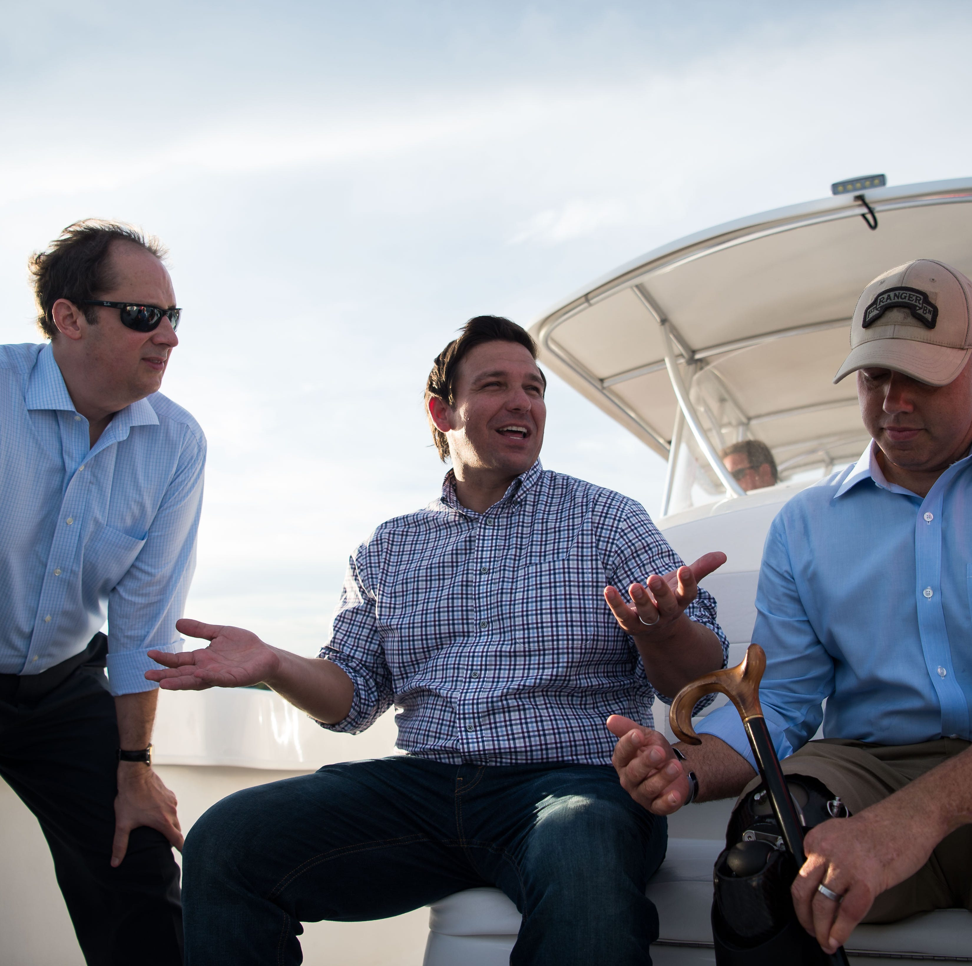 U.S. Reps. Ron DeSantis and Brian Mast take a boat ride out of Stuart, accompanied by Florida Sen. Joe Negron and other stakeholders, on Monday, Aug. 20, 2018, to see and discuss the algae crisis in the St. Lucie River.
