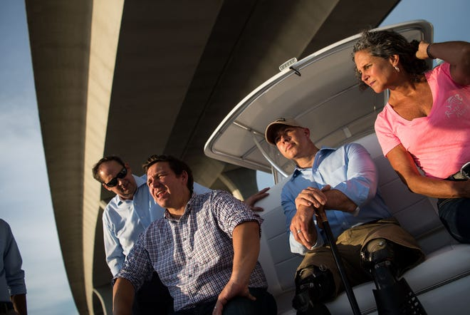 U.S. Reps. Ron DeSantis (left of center) and Brian Mast (right) pass under the Roosevelt Bridge during a boat ride out of downtown Stuart — accompanied by Florida Sen. Joe Negron, environmental advocate Jacqui Thurlow-Lippisch and other stakeholders — on Monday, Aug. 20, 2018, to see and discuss the algae crisis in the St. Lucie River.