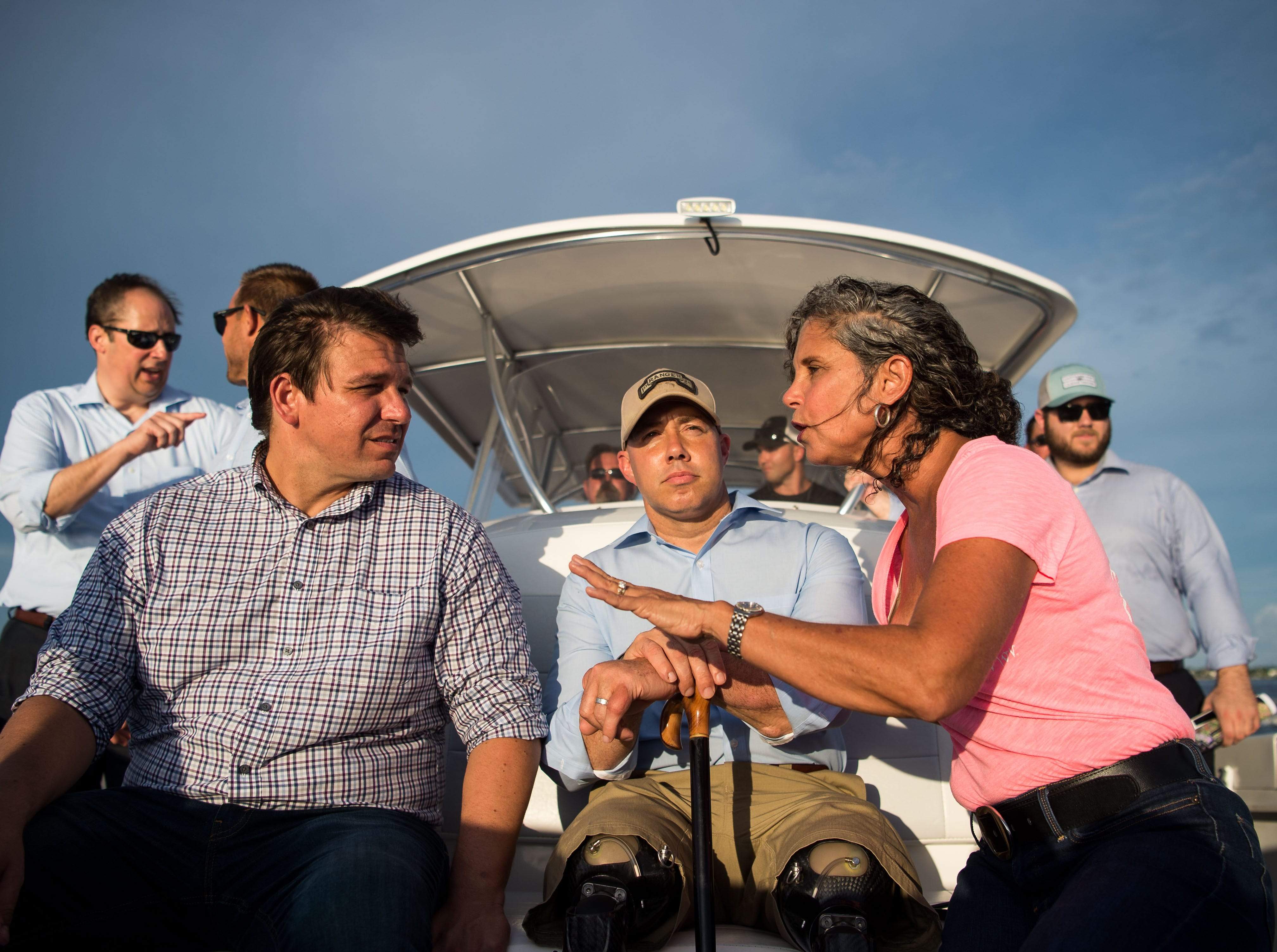 U.S. Reps. Ron DeSantis (left) and Brian Mast (center) speak with environmental advocate Jacqui Thurlow-Lippisch on Monday, Aug. 20, 2018, during a boat tour to see and discuss the algae crisis in the St. Lucie River.