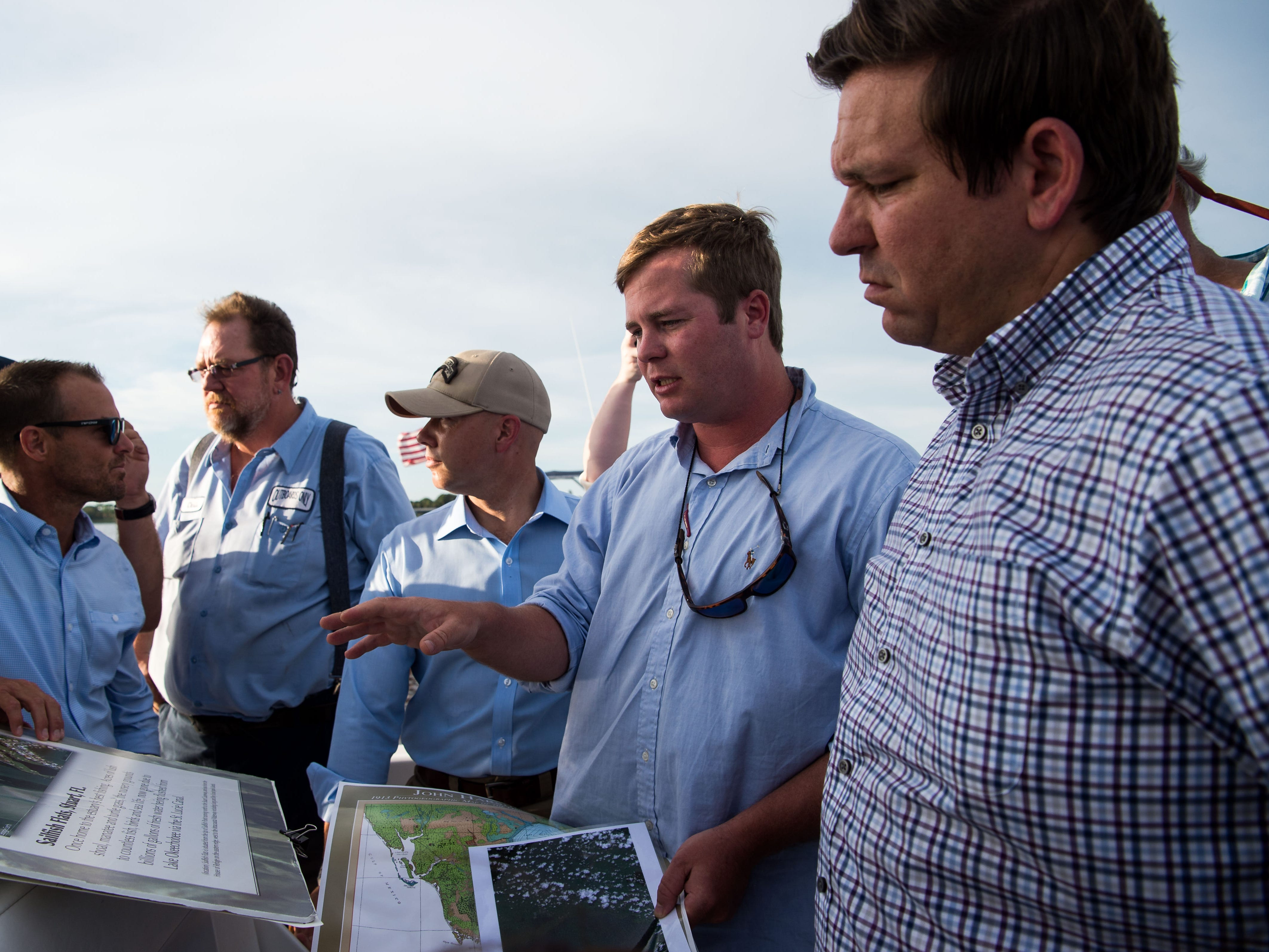Alex Gillen (right of center), of Stuart, with Bullsugar.org, talks about algal blooms on the St. Lucie River with U.S. Rep. Ron DeSantis (far right) during a boat ride out of downtown Stuart on Monday, Aug. 20, 2018, on the St. Lucie River. DeSantis is campaigning for the Republican nomination for governor.