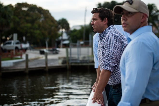 U.S. Reps. Ron DeSantis and Brian Mast (right) look out over the waters of the St. Lucie River during a boat ride out of Stuart on Monday, Aug. 20, 2018, to see and discuss the algae crisis.