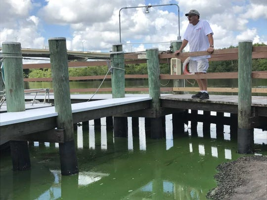 Tom Nolin, groundskeeper at Riverland Mobile Home Park in Stuart, watches Tuesday, Aug. 21, 2018, as algae-laden water that had flowed into the park's marina from the South Fork of the St. Lucie River flows back out.