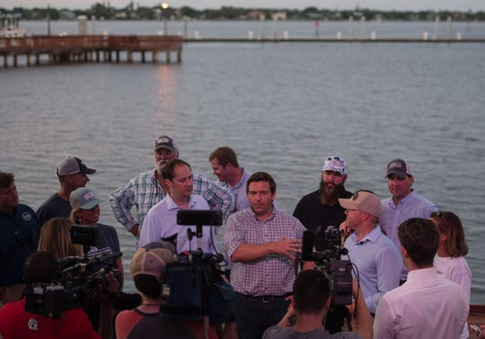 U.S. Rep. Ron DeSantis (center) speaks to news media gathered on the Riverwalk Stage in downtown Stuart on Monday, Aug. 20, 2018, after a boat ride with fellow Rep. Brian Mast (right) Florida Sen. Joe Negron (left), and other stakeholders, on the St. Lucie River. DeSantis is facing Florida Commissioner of Agriculture Adam Putnam — and others — in the Republican primary.
