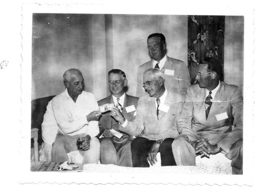 """The board of the First Federal Savings and Loan of Indian River County meet in August 1950 to discuss the status of the dollar. Warren T. Zeuch, from left front row, John J. Schumann, Tom Stewart and Earle Thatcher share comments while J.R. """"Rip"""" Graves stands over them."""