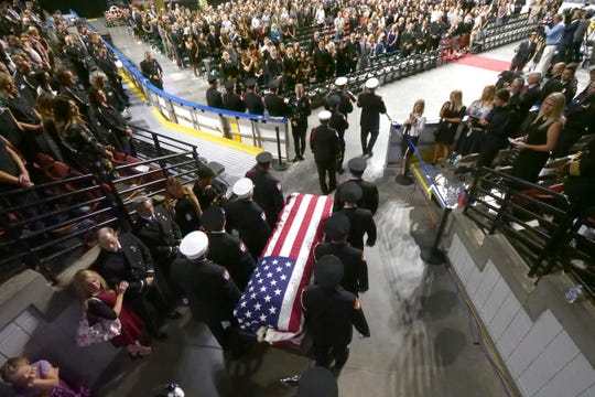 Firefighters carry the casket of Battalion Chief Matt Burchett of the Draper Fire Department into the Maverik Center during funeral services Monday in West Valley City, Utah. Burchett died while fighting a wildfire north of San Francisco. He was flown to a hospital where he succumbed to his injuries.