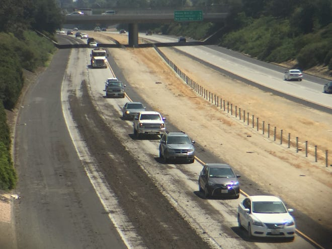 A load of asphalt narrows westbound traffic on Highway 198 to one lane between County Center and Akers.