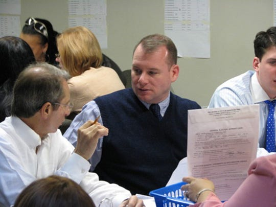 Attorney Guy Parisi, left, and other attorneys discuss an affidavit ballot offered for inspection by a Westchester County Board of Elections employee in White Plains in 2010. Counting in a disputed state Senate race were to continue through the weekend.