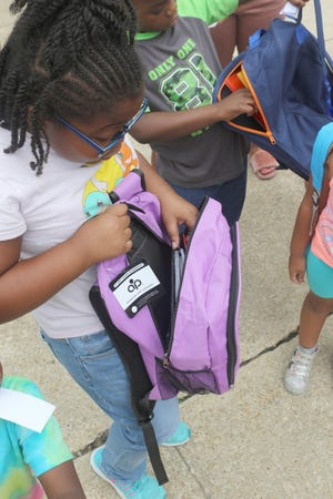 """A young girl shows off the new backpack and school supplies inside that she received Tuesday afternoon at Dover City Hall as part of the Marino Rivera Foundation's """"Back to School Backpack Giveaway""""  for students K-5."""