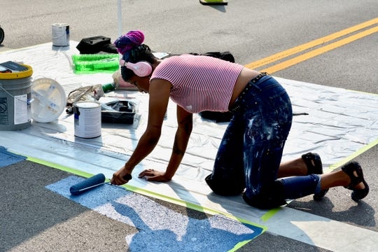Muralist and artist Brea'n Thompson began painting four 33 by 12 feet crosswalk murals Tuesday morning at the corner of Indiana and 7th Street. Part of the project will be done in time for Hotter'N Hell this weekend.