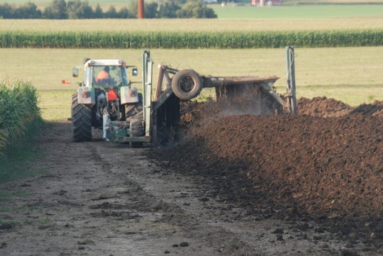 Farmers can build and turn compost windrows themselves on their farms using loader tractors or skid steers, but some may prefer to use the services of a custom operator with a dedicated tractor-driven implement like this one designed to turn compost piles.