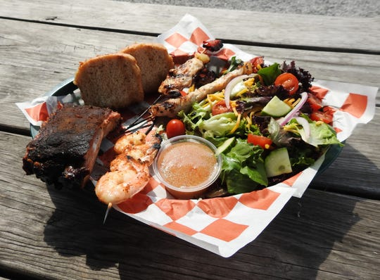 The dish shows off several items offered at the Smokehouse, including ribs, beer bread, grilled chicken skewers, salad and cajun grilled shrimp skewer.