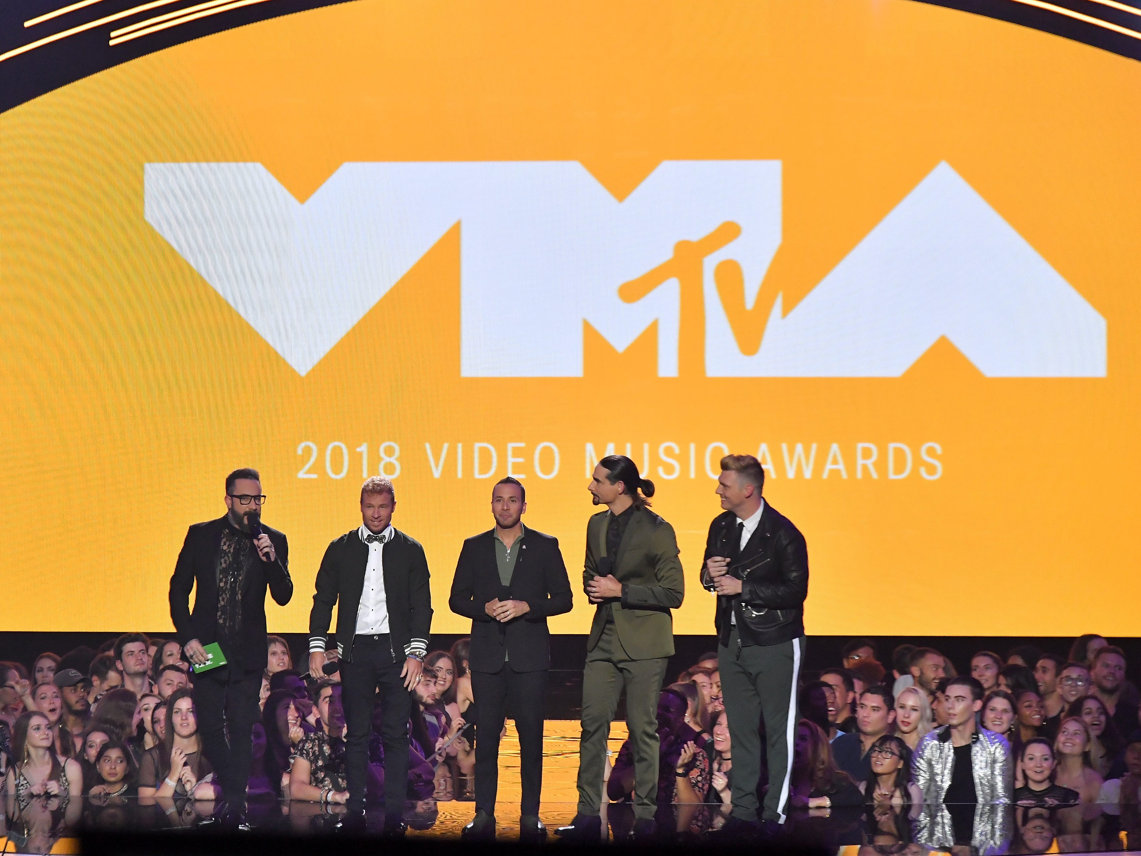 NEW YORK, NY - AUGUST 20: AJ McLean, Brian Littrell, Howie Dorough, Kevin Richardson and Nick Carter of Backstreet Boys speak onstage during the 2018 MTV Video Music Awards at Radio City Music Hall on August 20, 2018 in New York City.  (Photo by Michael Loccisano/Getty Images for MTV) ORG XMIT: 775210297 ORIG FILE ID: 1020371314