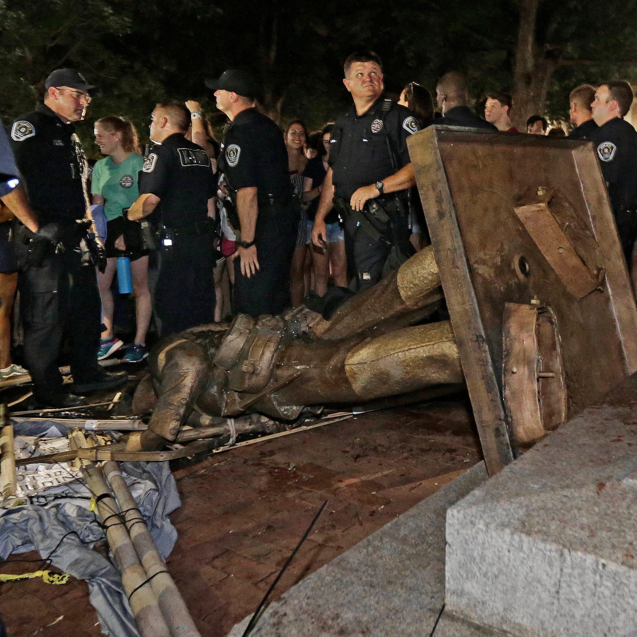 "Police stand guard after the confederate statue known as ""Silent Sam"" was toppled by protesters on campus at the University of North Carolina in Chapel Hill."