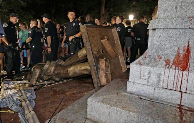 """Police stand guard after the confederate statue known as """"Silent Sam"""" was toppled by protesters on campus at the University of North Carolina in Chapel Hill."""