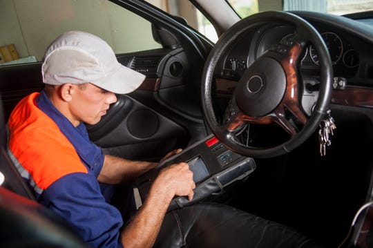 Car mechanic diagnosis the steering in auto repair service