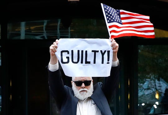 "Protester Bill Christeson holds up a sign saying ""guilty"" as the first count of guilty comes in at he trial of former Donald Trump campaign chairman Paul Manafort, at federal court in Alexandria, Va., Tuesday, Aug. 21, 2018."