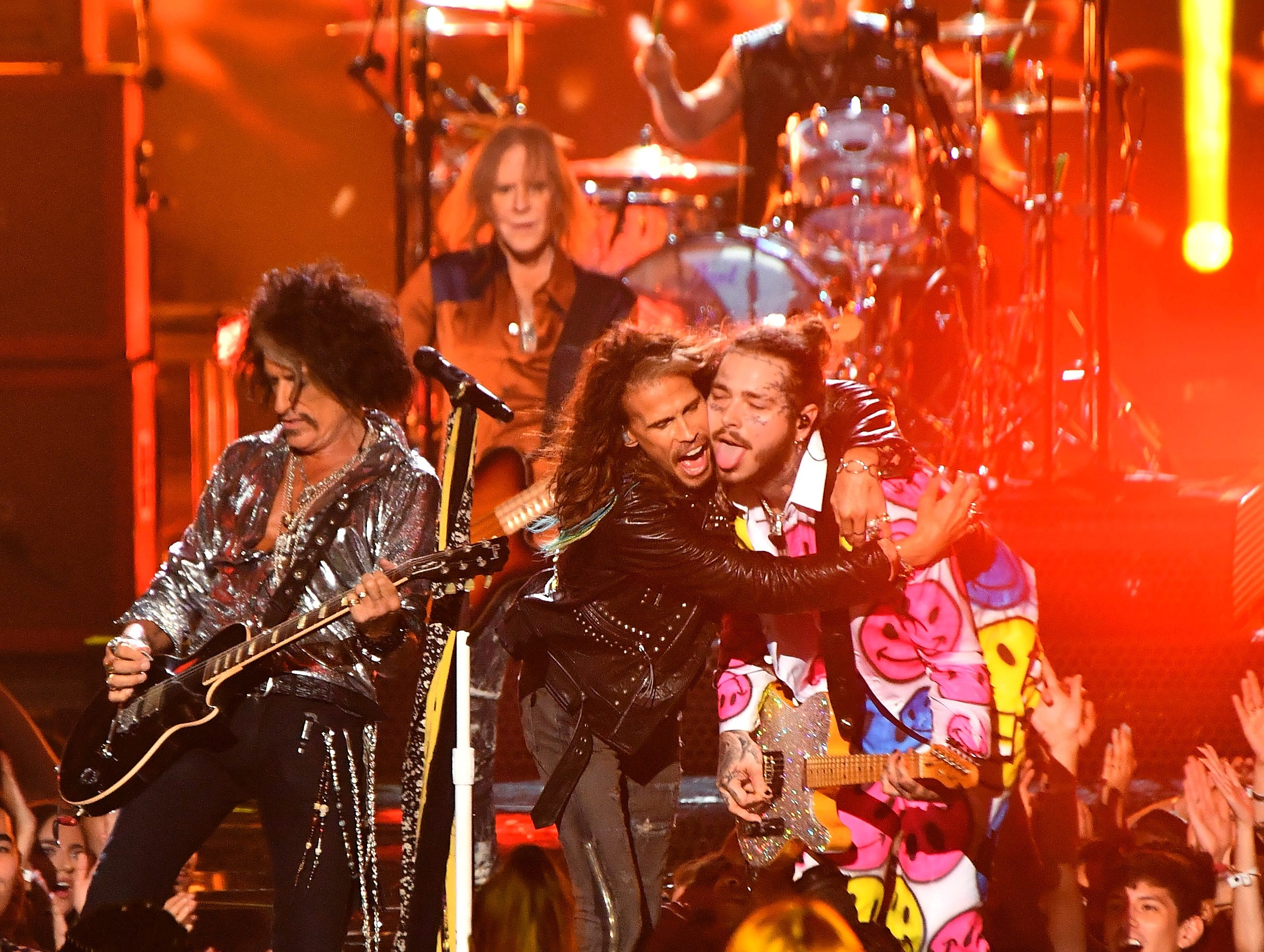 Joe Perry (left) and Steven Tyler of Aerosmith perform with Post Malone (right) onstage.