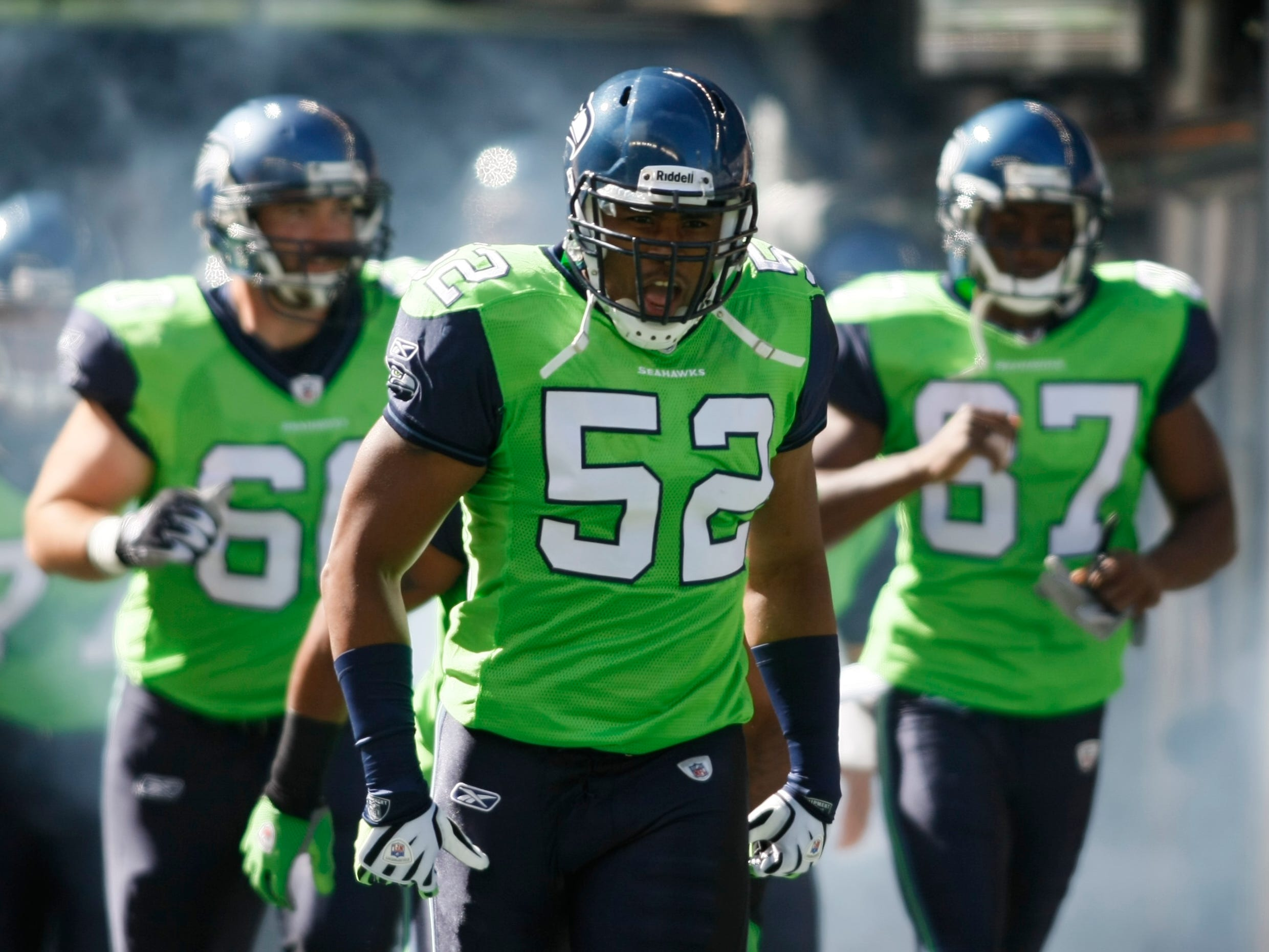 Wearing very bright green jerseys, Seahawks' D.D. Lewis (52) and teammates run onto the field in 2009.