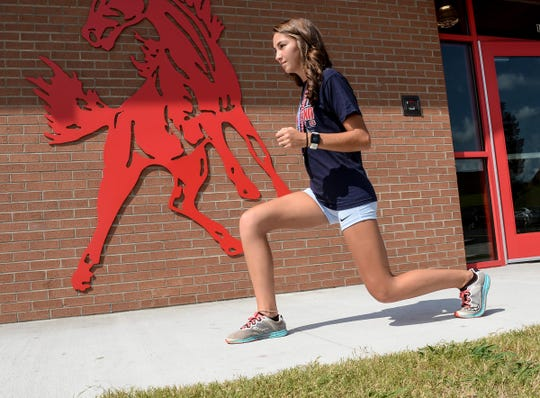 Morgan Roberts, a junior at Palmetto High School, stretches before practice at the school on Wednesday. She won two silver medals in cross country events in Australia this summer.